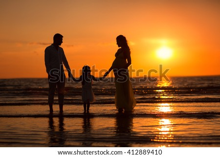 Pregnant mom in a dress, little girl and dad walking on the beach at sunset. silhouette