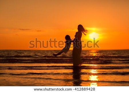 Pregnant mom in a dress playing with baby on the beach at sunset - stock photo
