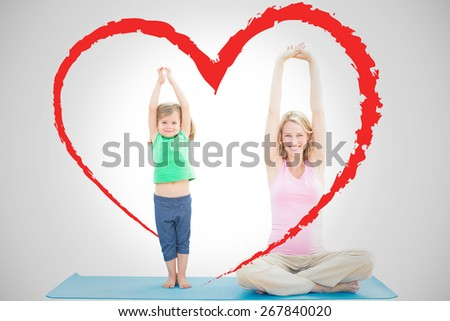 Pregnant mother and daughter doing yoga together against heart - stock photo