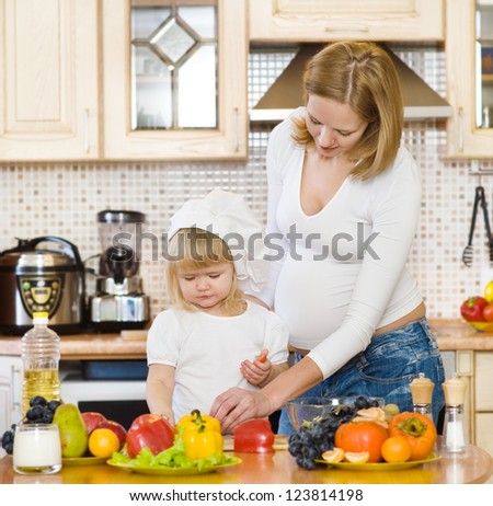 pregnant mother and daughter in kitchen