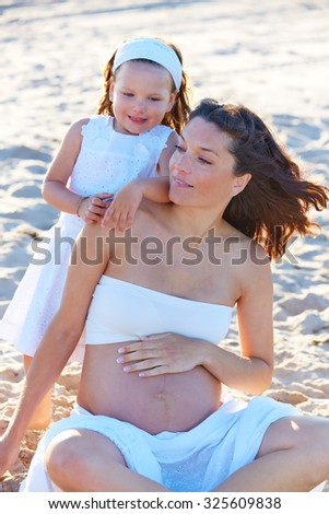 Pregnant mother and daughter on the beach together hug sitting on sand - stock photo