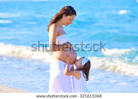Pregnant mother and daughter on the beach together kissing belly