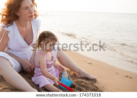 pregnant mother and daughter playing in beach sand of Mediterranean - stock photo