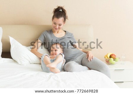 Pregnant mother and her child son are spending time together at home in bed. Little kid boy looking at mother pregnant tummy. Pregnancy, family, parenthood lifestyle concept