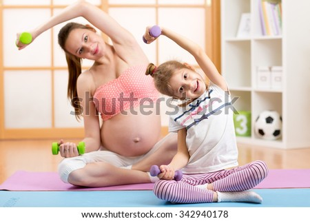 Pregnant mother and her daughter child doing gym exercises with dumbells home