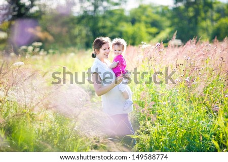 Pregnant mother and her toddler walking in a sunny meadow - stock photo
