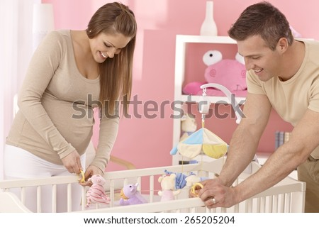 Pregnant mother and husband preparing baby's cot, smiling. - stock photo