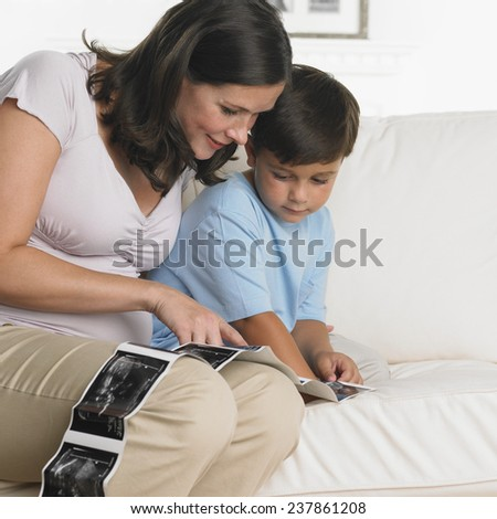 Pregnant Mother and Son Looking at Sonogram - stock photo