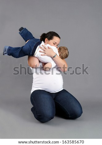 Pregnant mother playing and kissing her little boy or toddler.