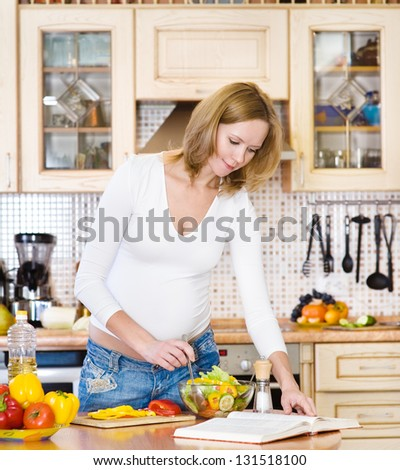 pregnant mother preparing food in kitchen and reading cooking recipe - stock photo