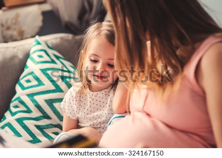 pregnant mother reading book to her toddler daughter at home, lifestyle series in real life interior - stock photo