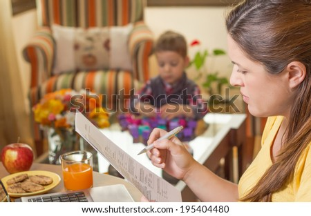 Pregnant mother reading business documents in a home office and his boring son playing on the background