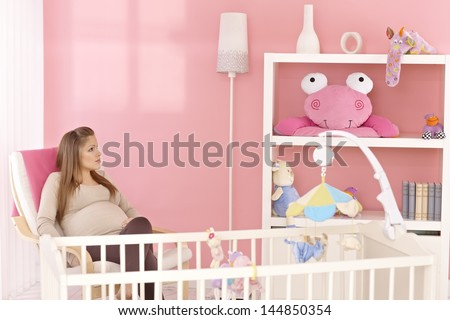 Pregnant mother sitting in armchair in pink baby's room, thinking. - stock photo