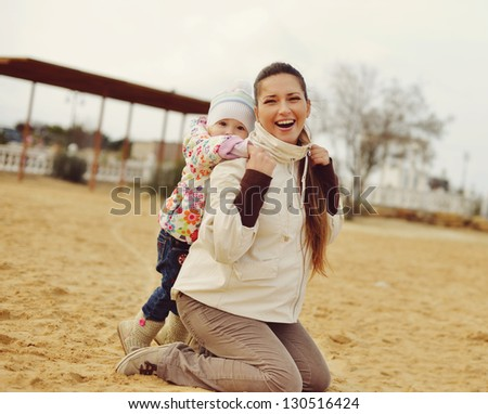 pregnant mother with baby daughter having fun on beach - stock photo