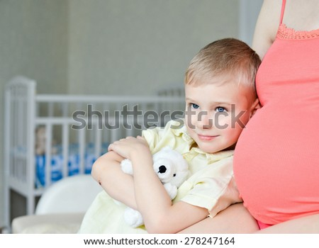 Pregnant mother with her cute little boy on the sofa at home