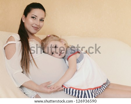 pregnant mother with loving daughter in soft selective focus - stock photo