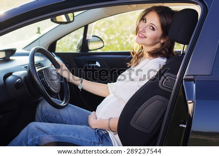 Pregnant smiling woman in driving seat of the car, sunset time - stock photo