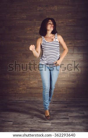 pregnant smiling woman in jeans dancing - stock photo