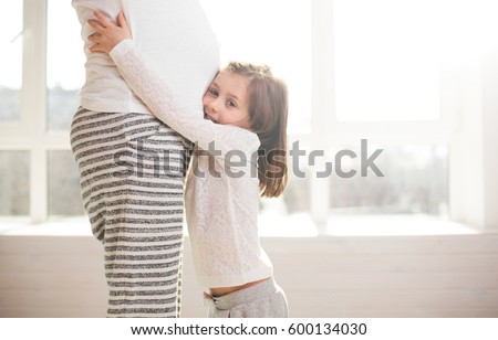 Pregnant woman and a child hugging