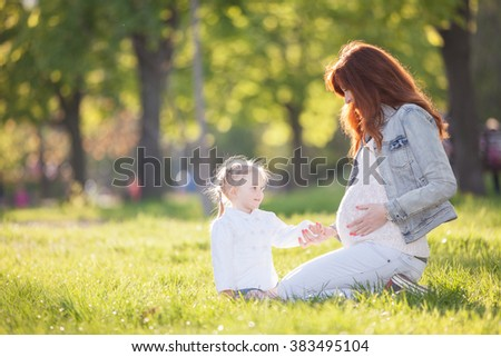 Pregnant woman and girl in the park - stock photo