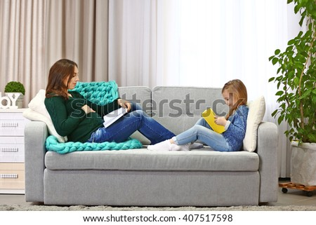 Pregnant woman and her child reading books on couch - stock photo