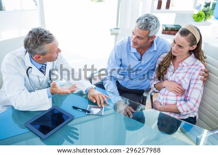 Pregnant woman and her husband discussing with doctor in clinic - stock photo