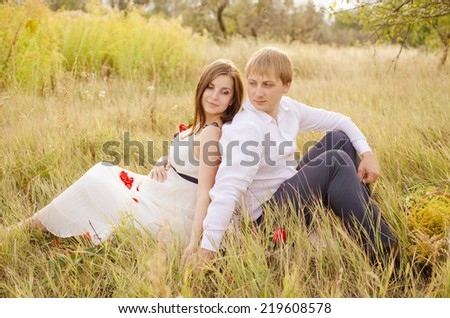 pregnant woman and her husband sitting back to back on grass and lovingly looking at each other - stock photo
