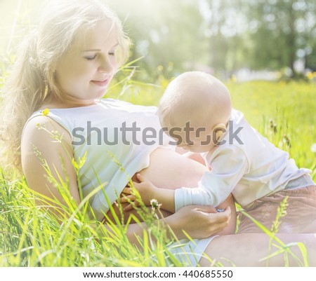 Pregnant woman and her little son in a meadow - stock photo