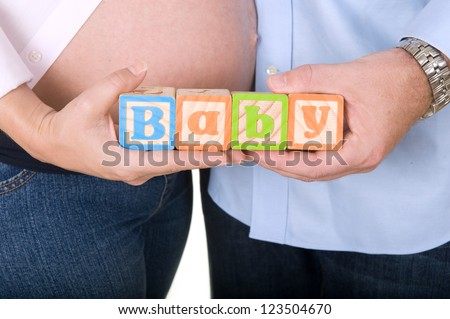 Pregnant woman and husband holding wooden blocks spelling baby - stock photo