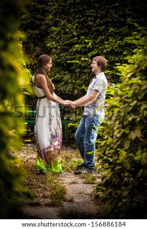 Pregnant woman and man holding hands in park - stock photo