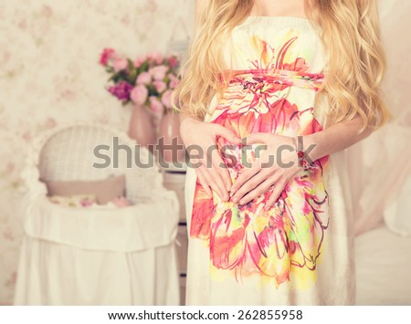 Pregnant woman at home. Woman put hands on his stomach in the form of the sign of the heart. Flowers and cot for the baby in the background. In anticipation of the birth of the baby. Close up. No face - stock photo