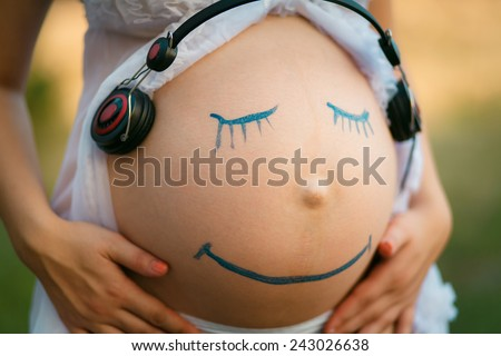 Pregnant woman belly closeup with smiling funny face drawing on it, listening to the music in earphones   - stock photo