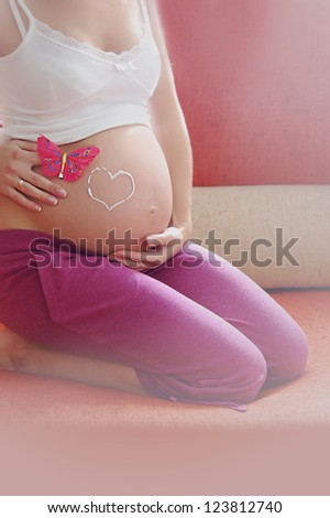 Pregnant woman belly with drawn love sign - stock photo