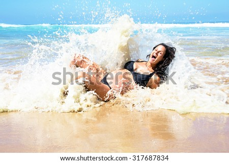 Pregnant woman caught in ocean waves - stock photo