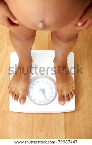 Pregnant woman checking her weight on scale - stock photo