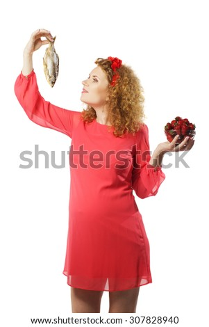Pregnant woman chooses between dried fish and strawberries  on isolated white background - stock photo