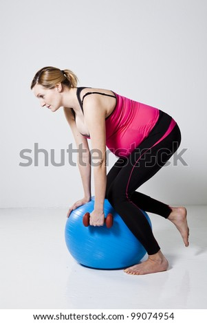 Pregnant woman doing a rowing exercise with dumbbells while kneeling on a fitness ball - stock photo