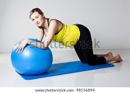 Pregnant woman doing an abdominal core strengthening exercise using a fitness ball on a mat