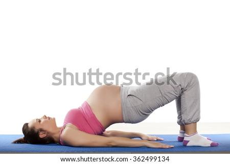 Pregnant woman doing exercises  on white background - stock photo