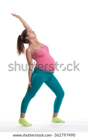 Pregnant woman doing yoga exercise and looking up. Pilates for pregnant. Pregnant woman in bright sportswear. - stock photo