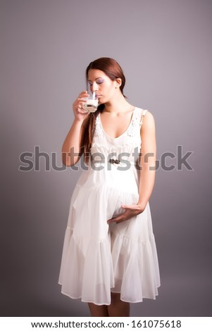 pregnant woman drinking milk - stock photo
