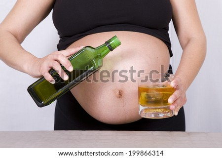 Pregnant woman drinking whisky. - stock photo