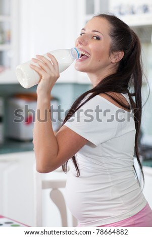 Pregnant woman drinks the milk on the house kitchen.