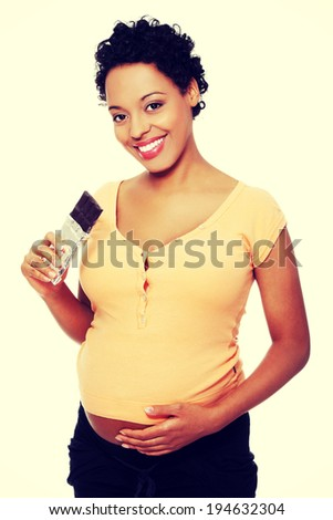Pregnant woman eating bar of chocolate - stock photo