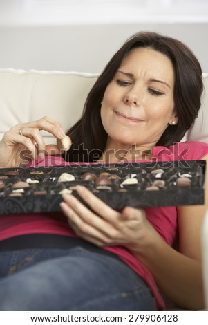 Pregnant Woman Eating Box Of Chocolates Sitting On Sofa At Home - stock photo