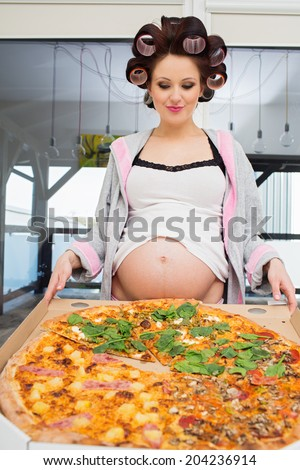 Pregnant woman eating pizza - stock photo
