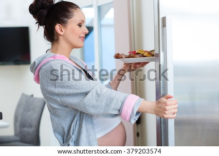 Pregnant woman eating sweets - stock photo