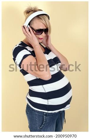 Pregnant woman enjoying the music - stock photo