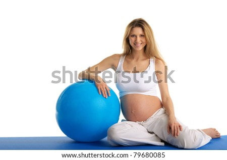 Pregnant woman excercises with gymnastic ball isolated in white