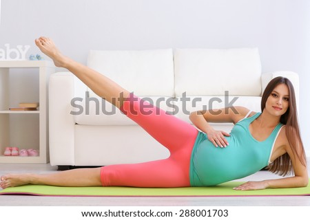 Pregnant woman exercising on green mat in room